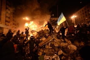 SState flag of Ukraine carried by a protester to the heart of developing clashes in Kyiv, Ukraine. Events of February 18, 2014.